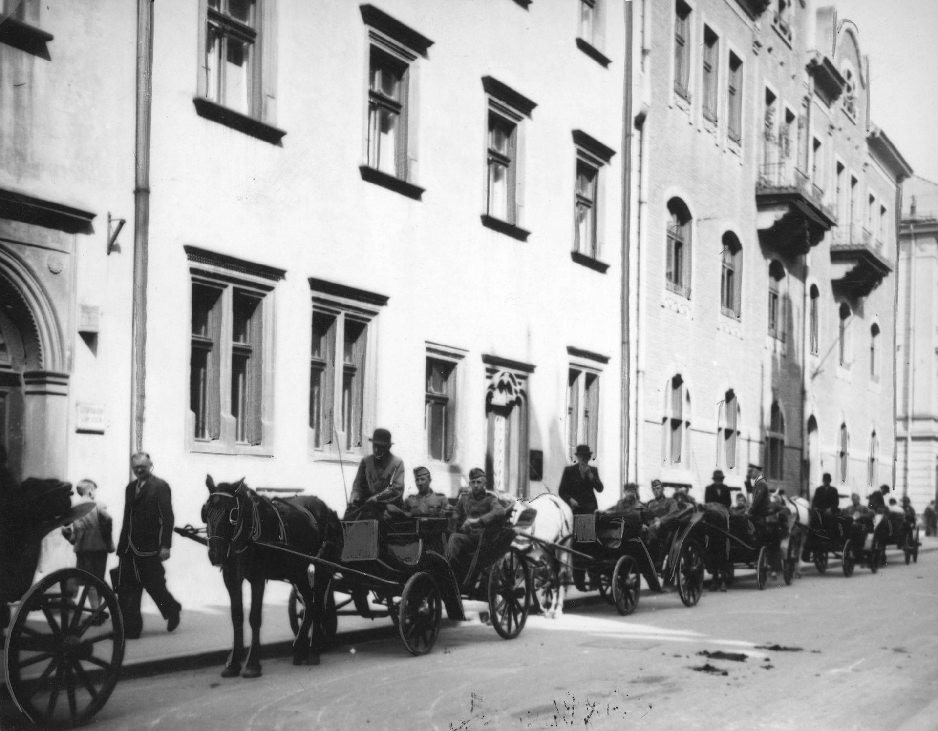 Niemieccy żołnierze zwiedzają Kraków w dorożkach. Zdjęcie zrobiono ok. 1941 roku. Źródło: Narodowe Archiwum Cyfrowe.