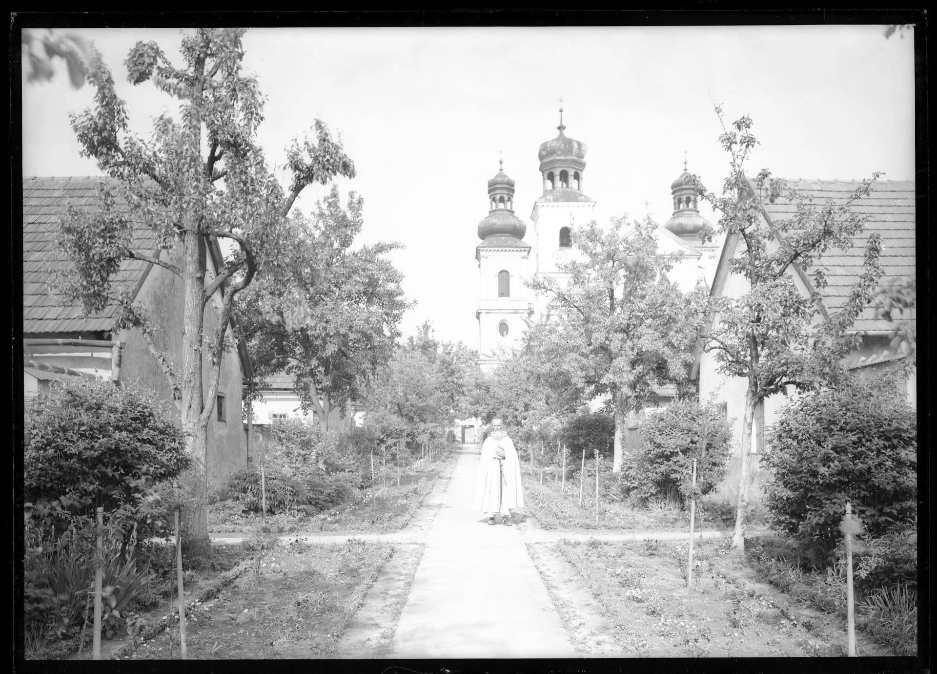 Zakonnik w ogrodzie, obok budynki przy kościele i klasztorze Kamedułów. 1934 rok. Fot. Narodowe Archiwum Cyfrowe.