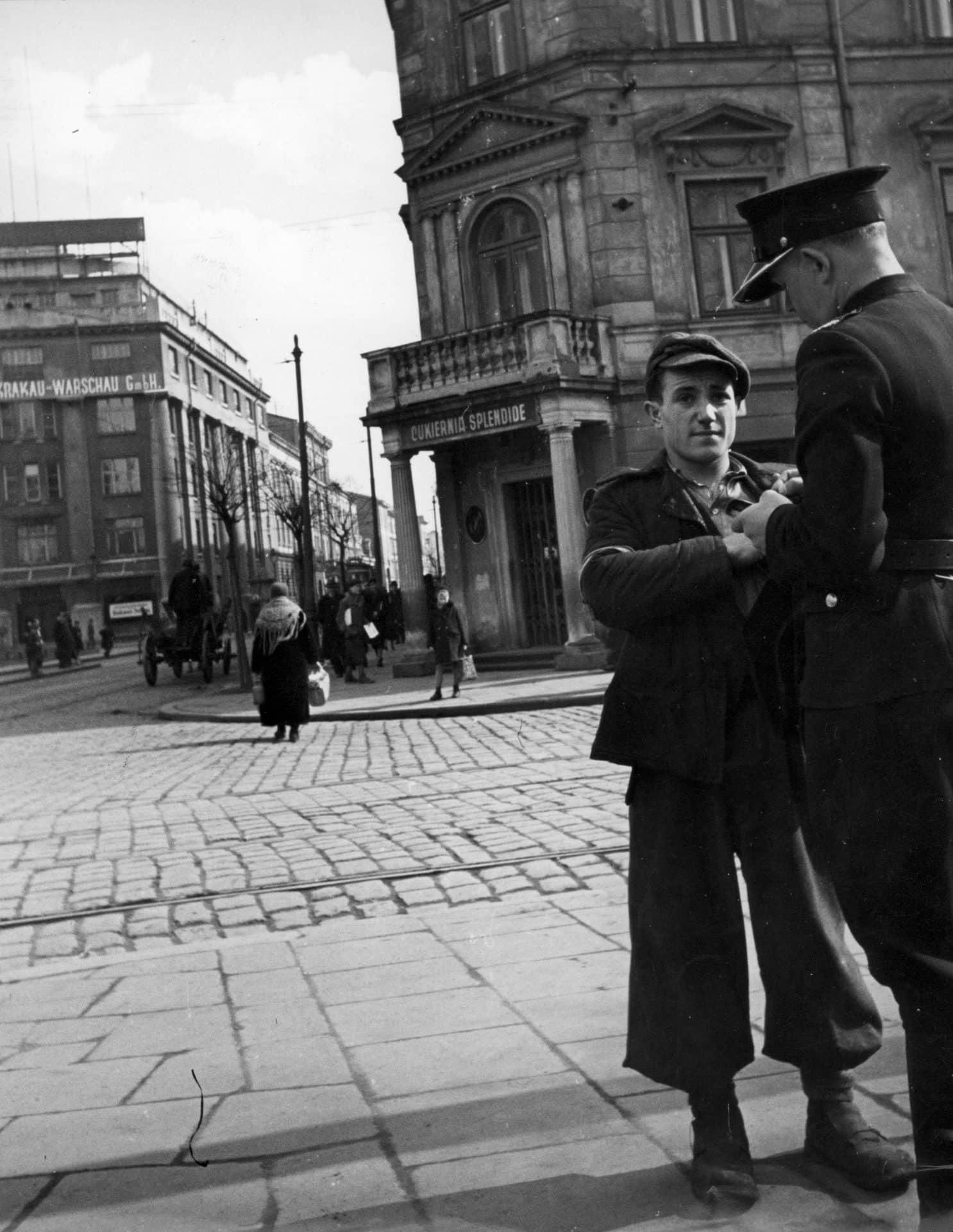 Policjant polski (granatowy) daje mandat przechodniowi za nieprzepisowe przechodzenie przez ulicę. Źródło: Narodowe Archiwum Cyfrowe. Niemiecka okupacja w Krakowie