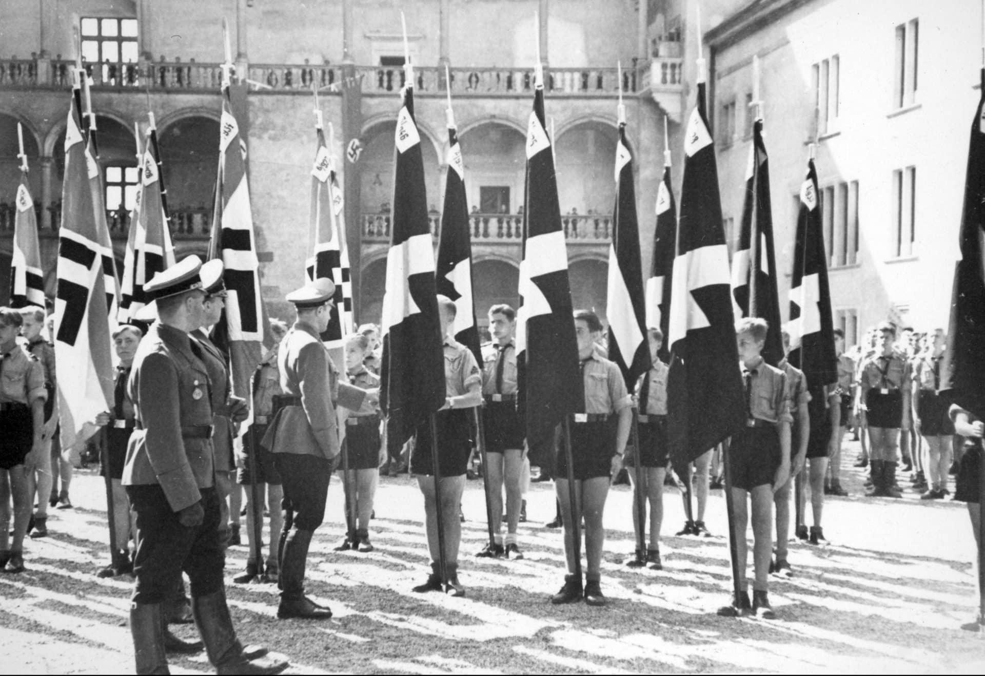 Arthur Axmann (pierwszy z prawej), Hans Frank (drugi z lewej) i Forschle przed pocztami sztandarowymi Hitlerjugend na dziedzińcu Zamku Królewskiego w Krakowie. Źródło: Narodowe Archiwum Cyfrowe. Niemiecka okupacja w Krakowie