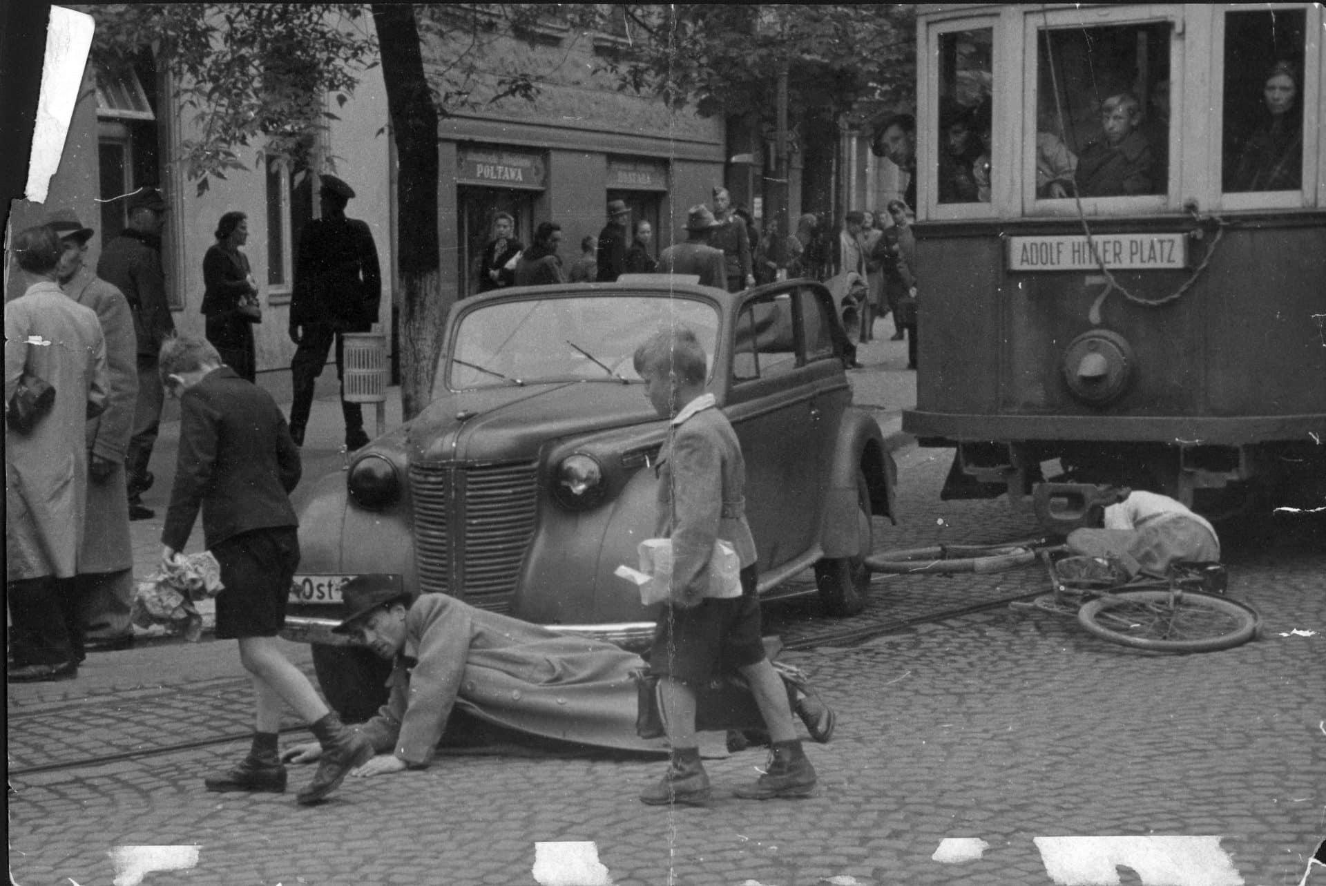 Wypadek z udziałem tramwaju typu SW1, samochodu osobowego, rowerzysty i pieszego. Fotografia pozowana. Na tramwaju widać tabliczkę Adolf Hitler Platz. Źródło: Narodowe Archiwum Cyfrowe.  Niemiecka okupacja w Krakowie
