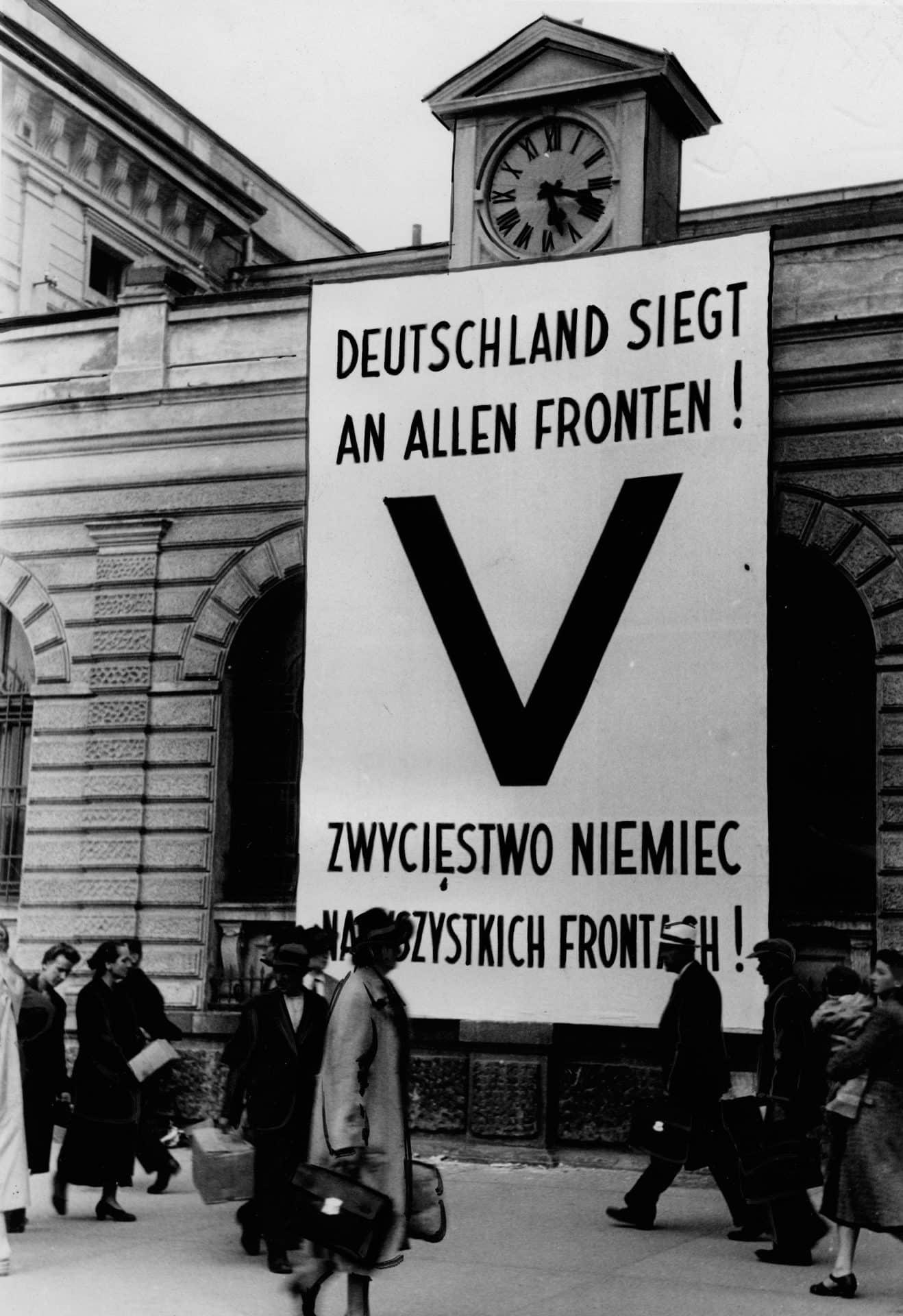 Rozwieszony na budynku plakat z symbolem Victorii. Źródło: Narodowe Archiwum Cyfrowe. Niemiecka okupacja w Krakowie