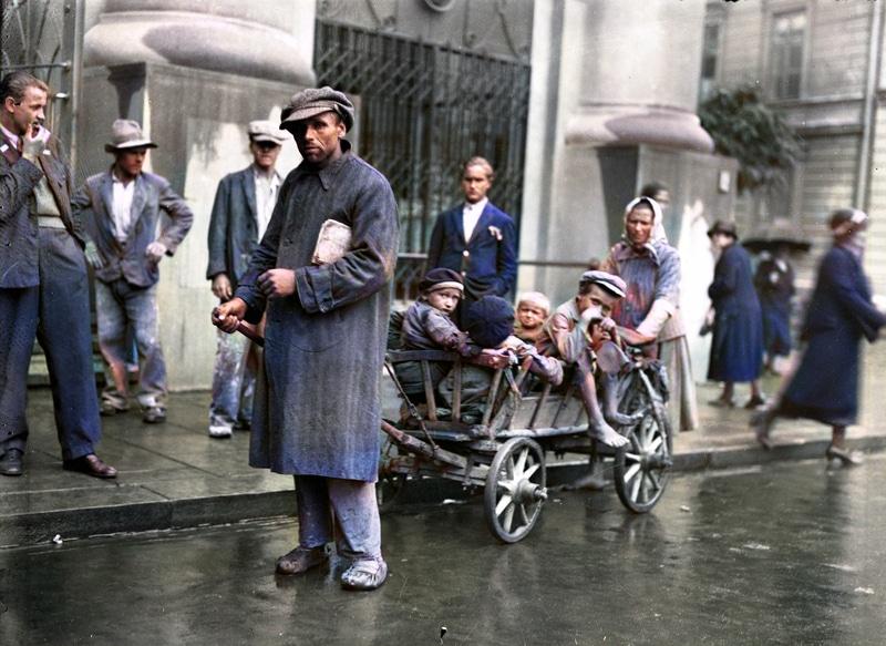Członkowie rodziny bezrobotnego z drewnianym wózkiem na jednej z ulic Krakowa. 1932 rok. Źródło: Narodowe Archiwum Cyfrowe.