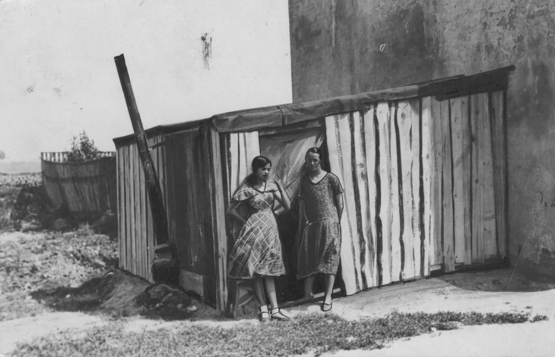 Dwie młode kobiety z bezrobotnej rodziny przed drewnianą szopą służącą za mieszkanie. Fot. Narodowe Archiwum Cyfrowe.