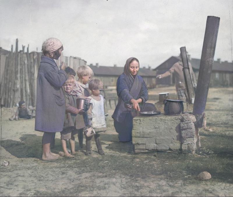 Grupa dzieci na dworze przy prowizorycznej kuchni, na której kobieta przyrządza posiłek. 1934 rok. Źródło: Narodowe Archiwum Cyfrowe.