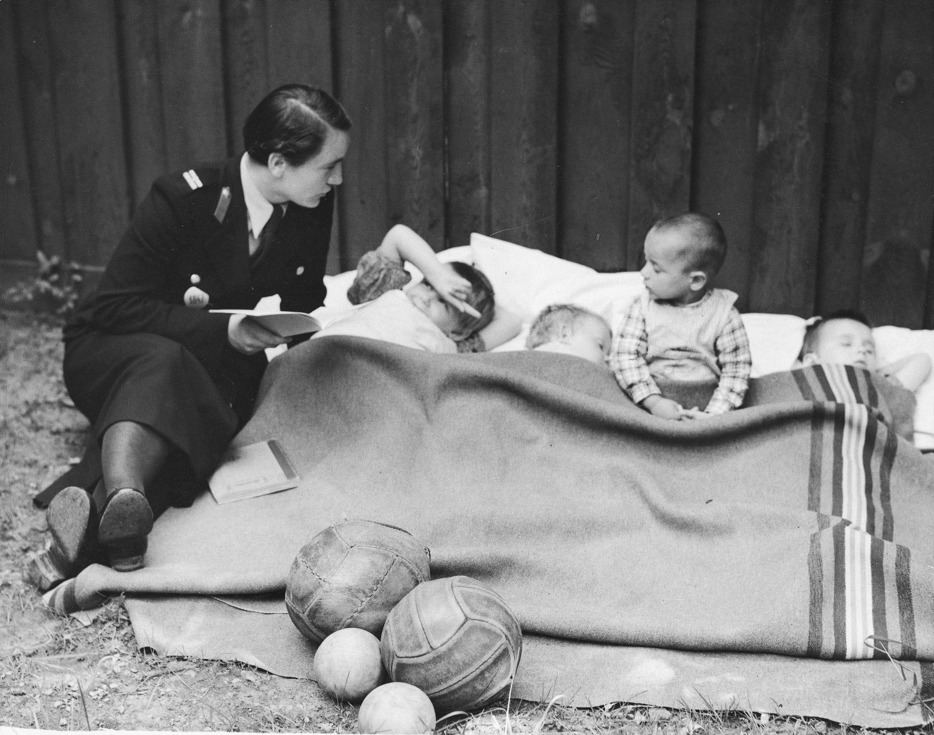 Policjantka czyta dzieciom przebywającym w Izbie Dziecka. 1937 rok. Fot. Narodowe Archiwum Cyfrowe.