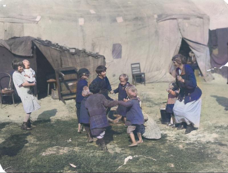 Grupa dzieci z bezrobotnych rodzin podczas zabawy przed prowizorycznymi namiotami mieszkalnymi na Żoliborzu. Źródło: Narodowe Archiwum Cyfrowe.