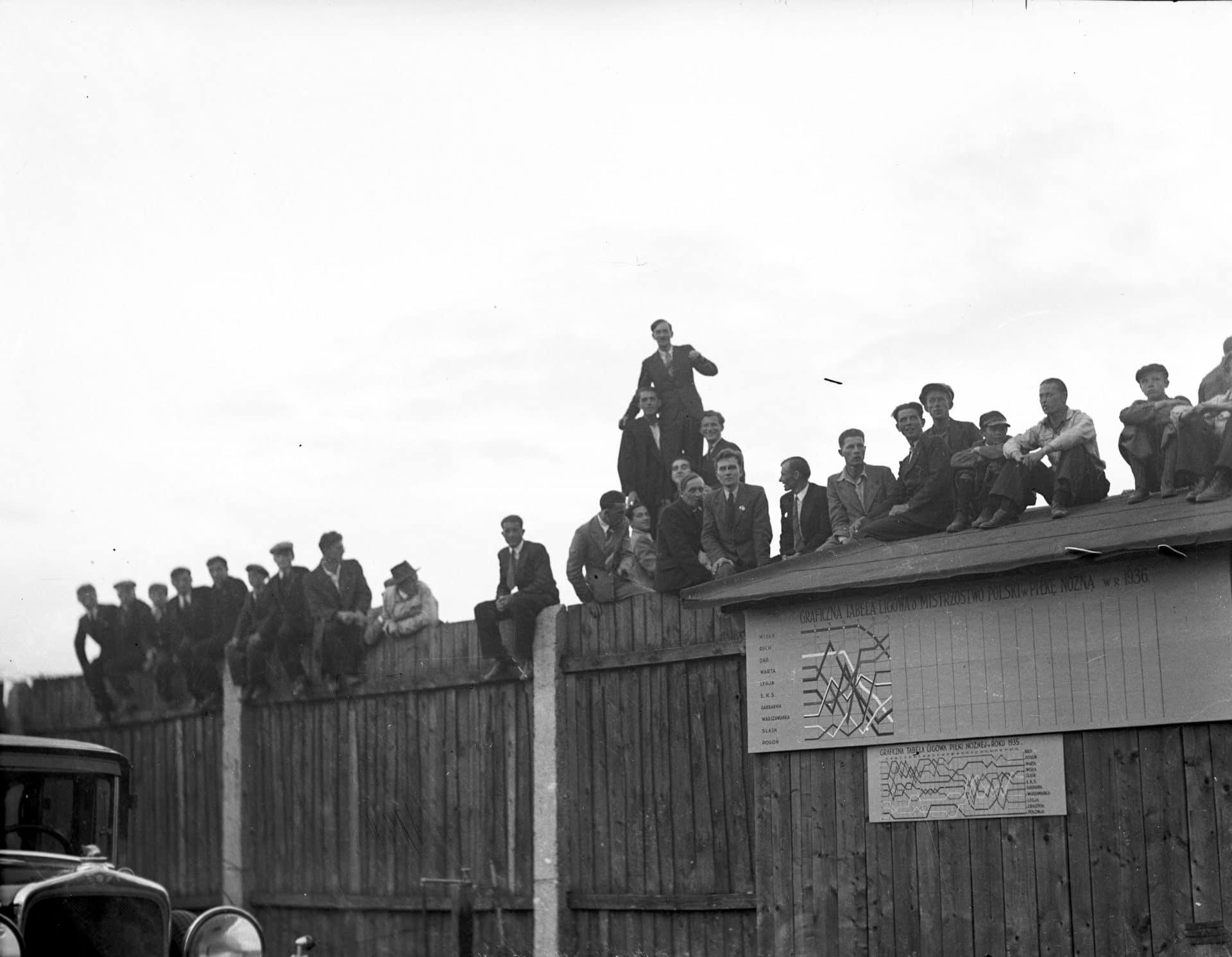 Siedzący na płocie kibice oglądają mecz Wisła - Chelsea, który rozegrano w 1936 roku. Źródło: Narodowe Archiwum Cyfrowe.