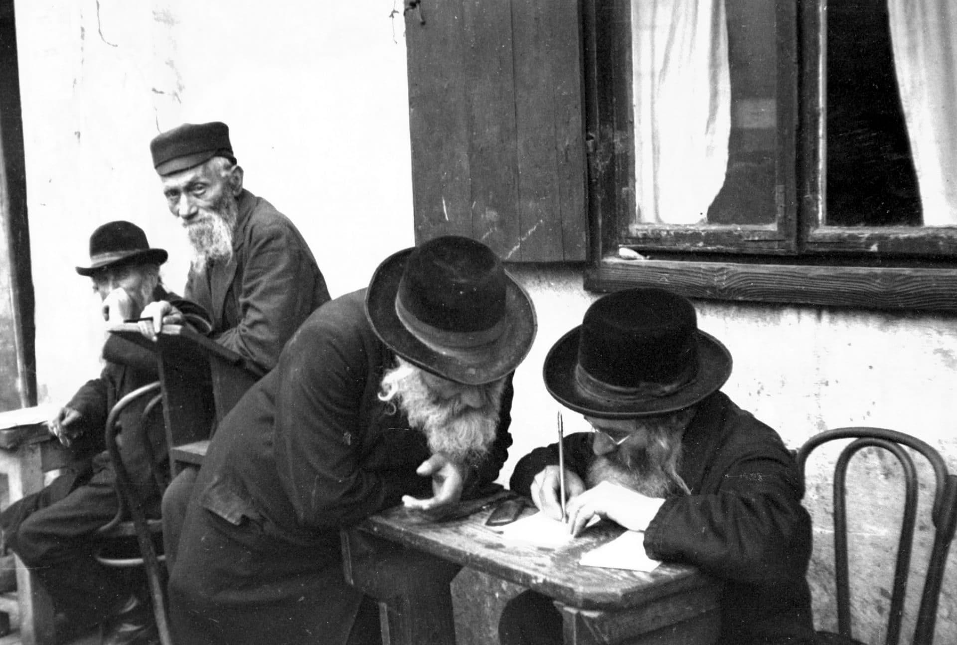 Uczestnicy uroczystości święta rabina ReMU podczas pisania próśb na kartkach umieszczanych w szczelinach grobowców rabinów. 1931 rok. Fot. Narodowe Archiwum Cyfrowe.